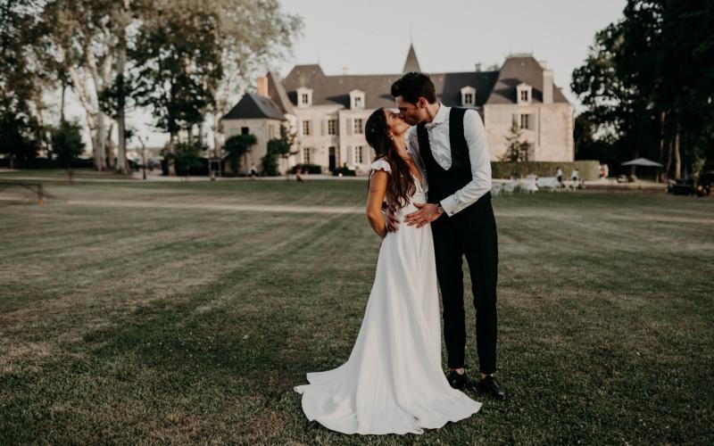 Portfolio des mariés Morgane & Ladislas qui s'embrassant avec le chateau de planchevienne en fond